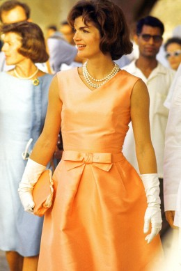 image: First Lady Jackie Kennedy wearing a fitted silk apricot dress and triple strand of pearls, walking through crowds at Udaipur during visit to India