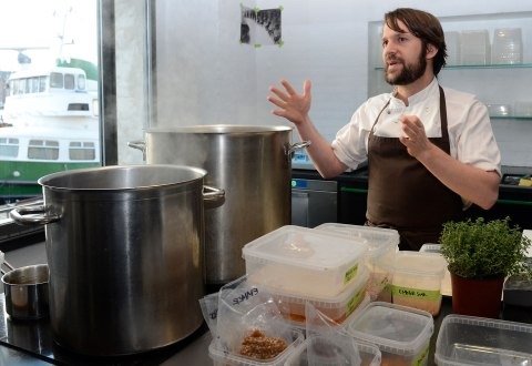 Rene Redzepi, chef and co-owner of the restaurant Noma, talks with his employees in a test kitchen in his restaurant in Copenhagen on Oct. 25, 2012.