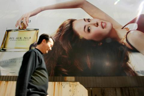 A man walks past a billboard advertising