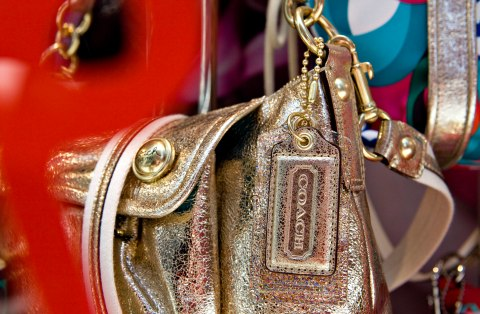 A Coach handbag sits on display in the window of a Coach sto