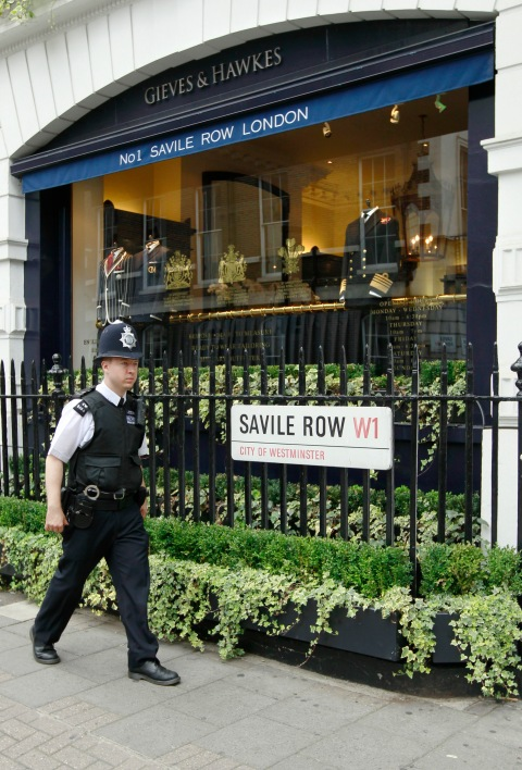 A police officer passes Gieves and Hawkes on Savile Row in London
